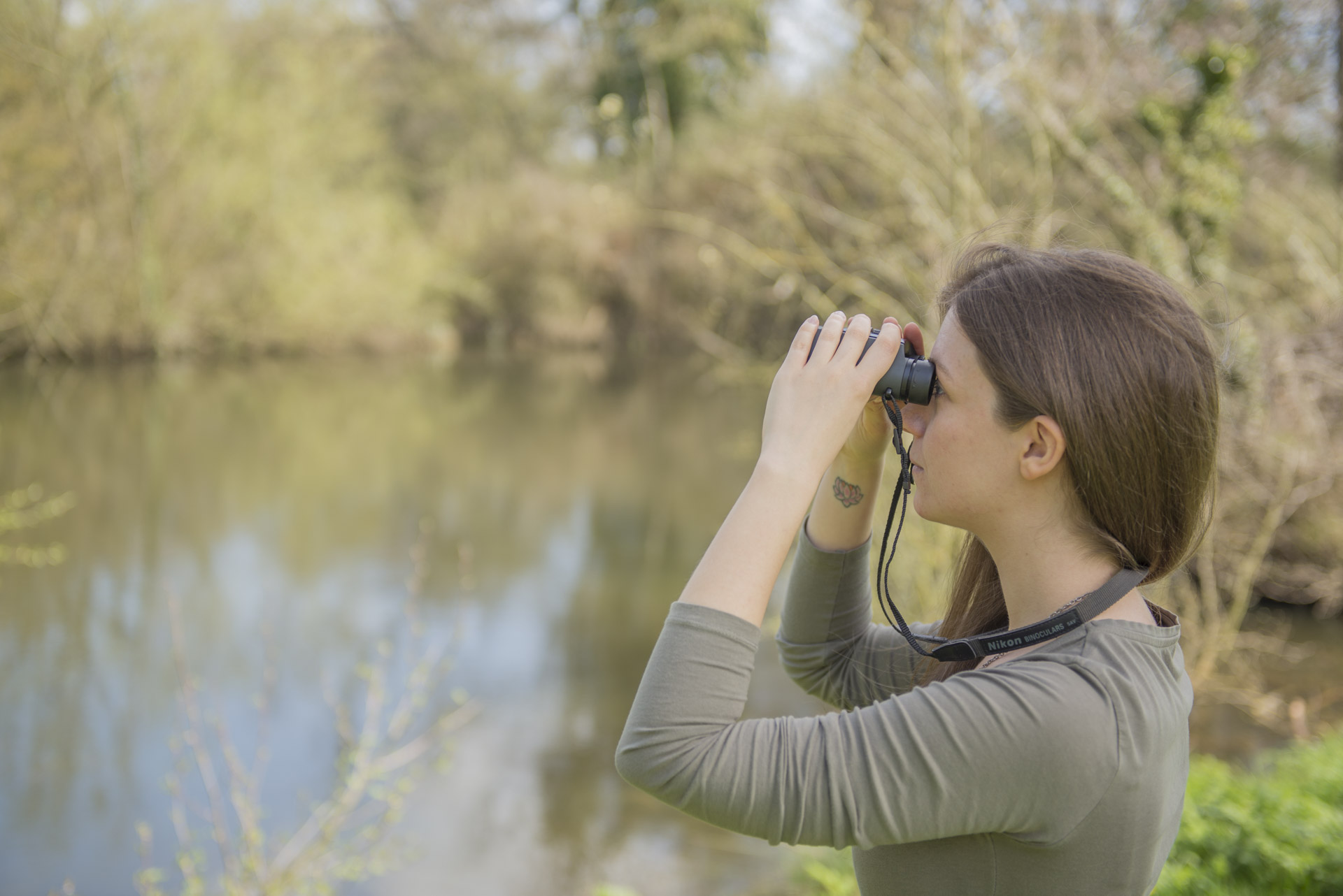 Emma Checkley, Ecologist at Wharton Natural Infrastructure Project, identifying birdlife at the nature reserve pond.